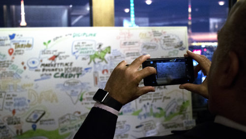 a participant takes a photo of an imagethink graphic recording.